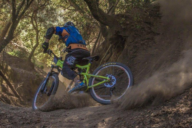 Mountainbikefahrer fährt einen Trail hinab. Er fährt mit seinem grün gefärbten Fully und wirbelt den Boden auf. Natürlich trägt der Fahrer seine Schutzbekleidung, wie Helm, Ellenbogen- und Knieschützer.