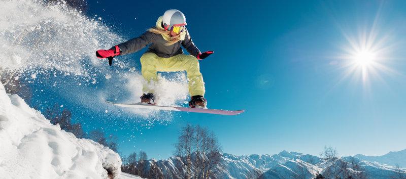 Sprung mit dem Snowboard von einer Frau