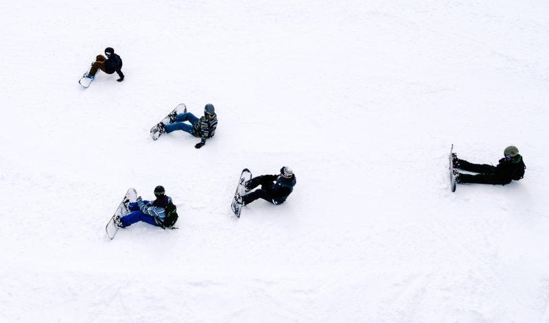 Auf der Skipiste sitzende Snowboardfahrer