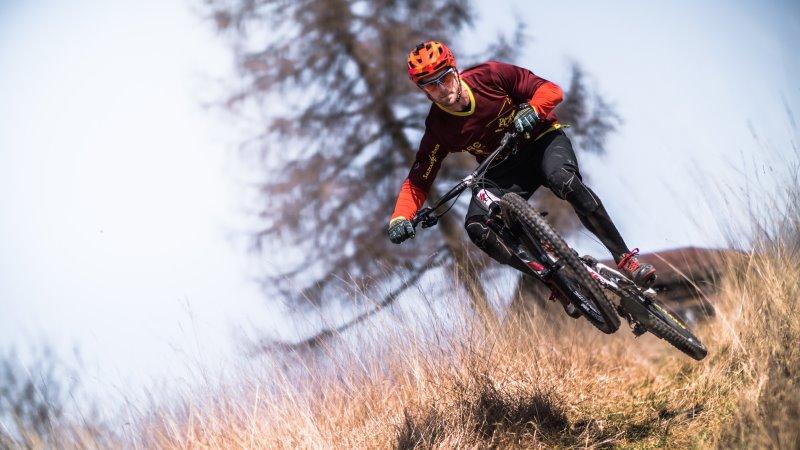 Trailbike-Fahrer der einen Berg runter fährt