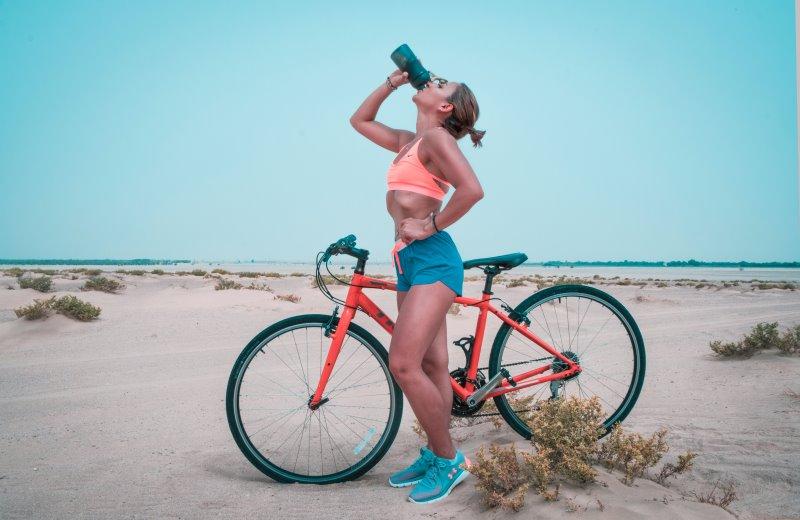 Eine Frau steht neben einem Fahrrad und trinkt etwas aus einer Flasche