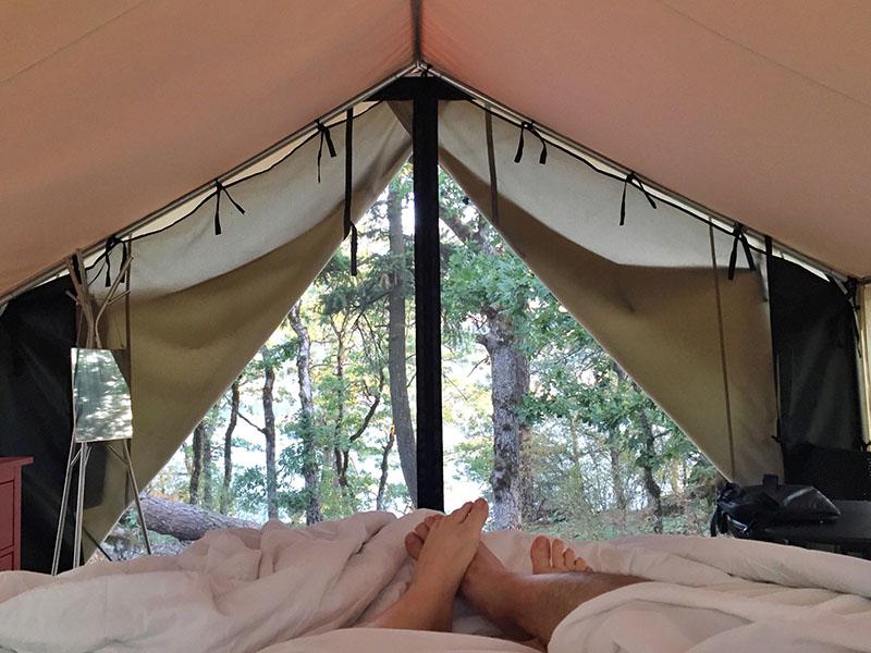 Zwei Personen in einem Baumwollschlafsack eingewickelt liegen im Zelt
