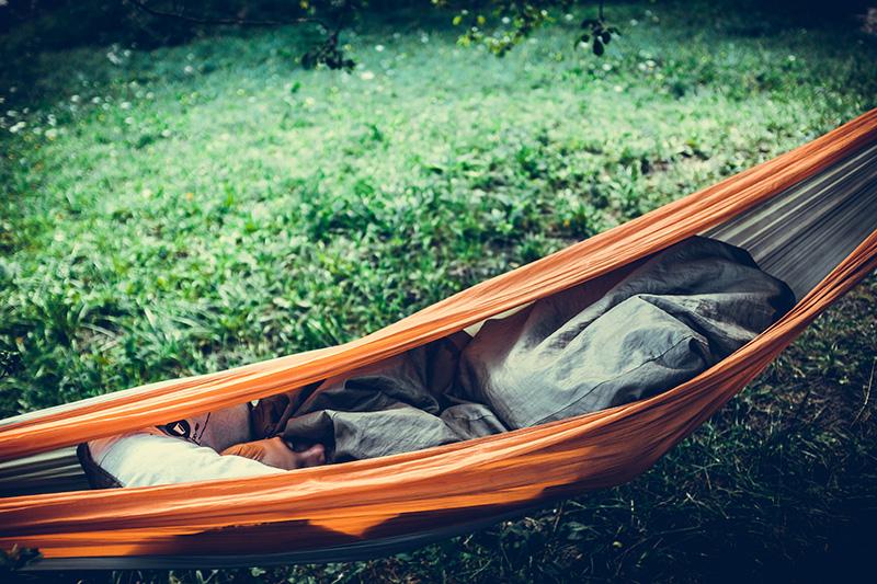 Person mit Schlafsack in einer Hängematte