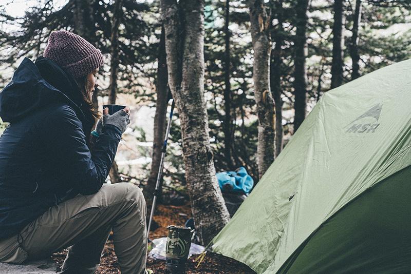Frau mit einer Tasse vor einem Zelt
