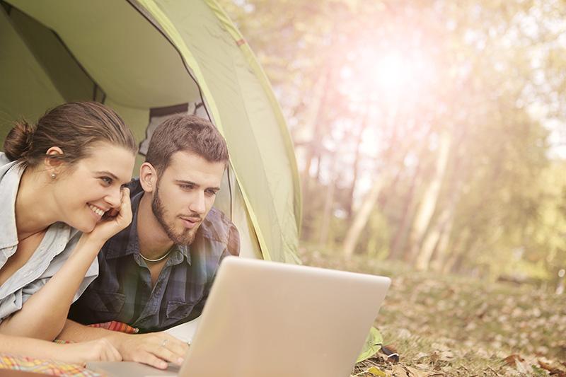 Zwei Personen die im Zelt liegend auf einen Laptop schauen