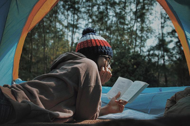 Frau liest in einem Zelt ein Buch