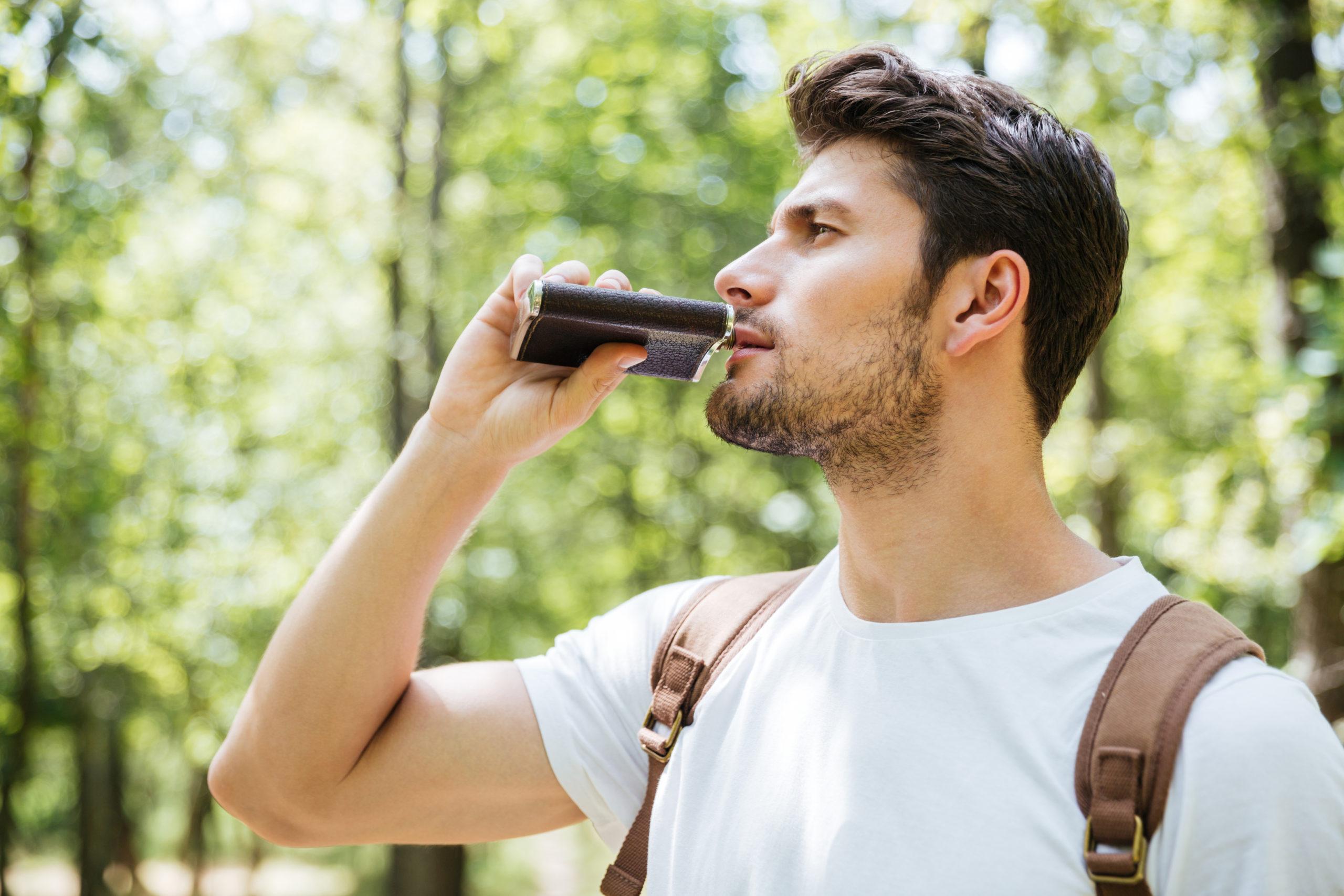Ein Mann der aus seinem Flachmann trinkt