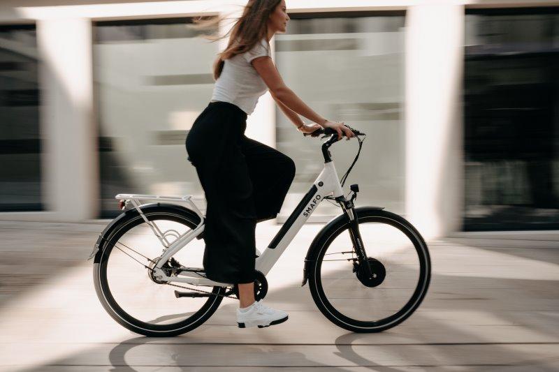 Eine Frau auf dem E-Bike mit Tiefeinsteiger Rahmen. Sie fährt an einem warmen Tag, mit dem SMAFO durch die Straßen. Das Design des E-Bikes ist in schwarz und weiß gehalten.