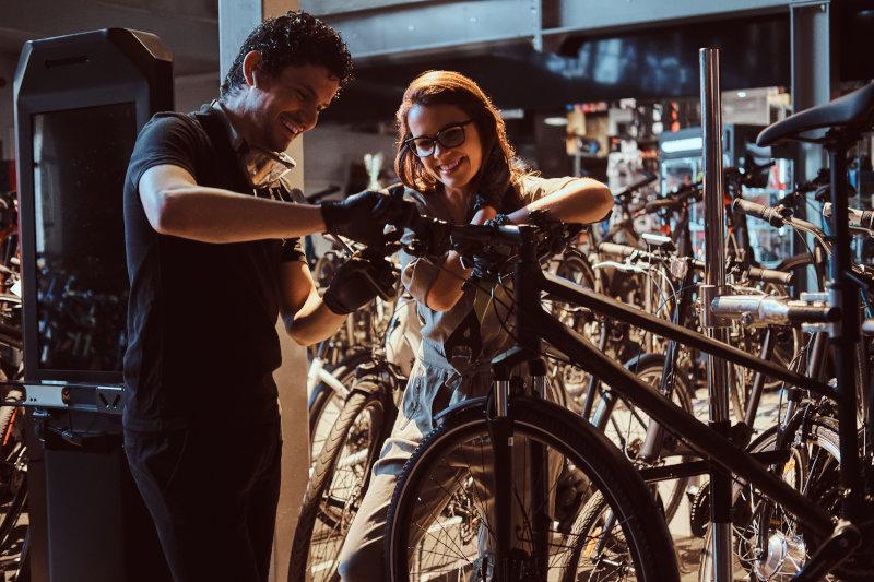 Viele Fahrräder mit einem Geschäft in Hintergrund. Ein Mann und eine Frau schrauben am Lenker des Fahrrads, welches in einer Montage hängt.