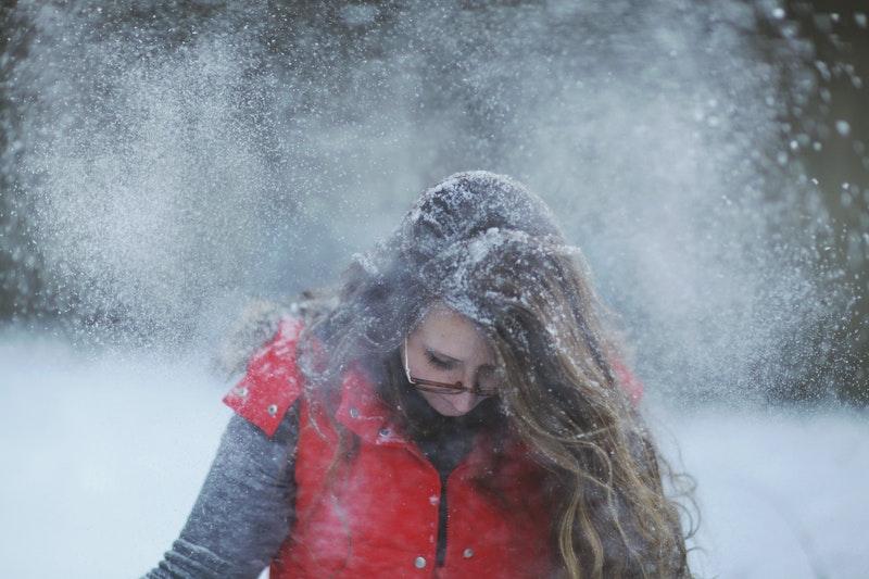 Frau in Weste im Schneegestöber