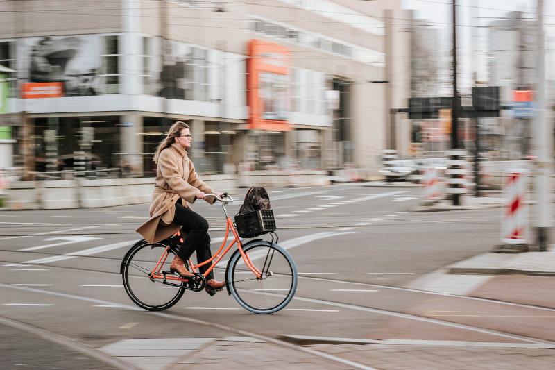 Eine Frau fährt auf einem orangefarbenen Hollandrad durch die Innenstadt