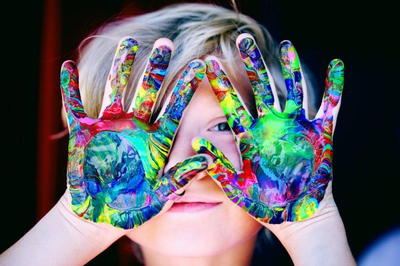 Kind mit Temperafarben an den Händen