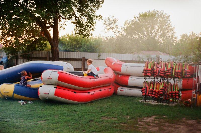 Zwei Kinder sitzen auf verschiedenen Schlauchbooten und daneben hängen Schwimmwesten.