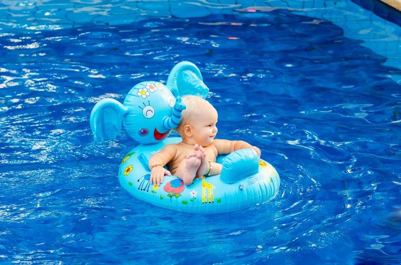 Ein Baby sitzt in einem kleinen Kinderschlauchboot mit dem Design eines Elefanten