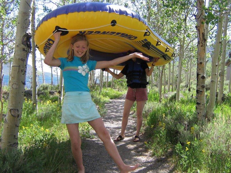 Zwei Mädchen tragen ein gelb-blaues Kinderschlauchboot und im Hintergrund sieht man ein Meer