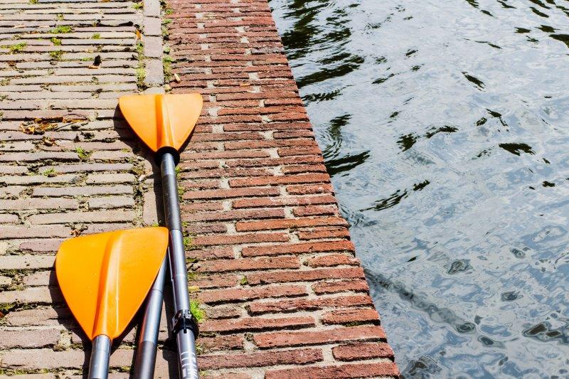 Orange Paddel für ein Kinderschlauchboot liegen am Boden neben einem Gewässer