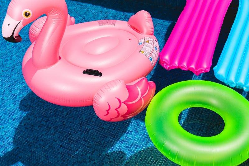 Ein Kinderschlauchboot schwimmt zusammen mit anderen luftgefüllten Spielzeugen auf dem Wasser