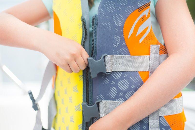 Ein Kind zieht sich eine Schwimmweste für das Spielen im Kinderschlauchboot an