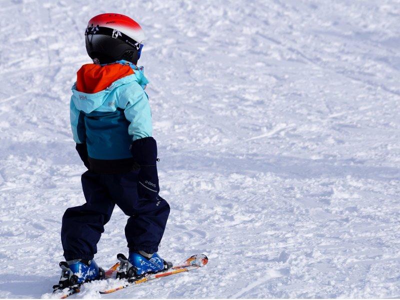 Kind steht mit einem Kinderskihelm auf einer Skipiste