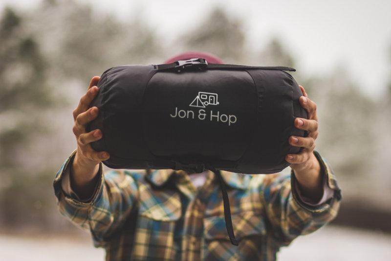 Mann hält komprimierten Schlafsack im Packsack vor die Kamera