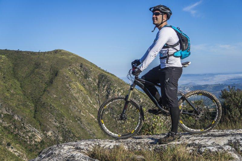 Mountainbikefahrer genießt die Aussicht. Dabei befindet er sich in schöner Landschaft an einem sonnigen Tag.