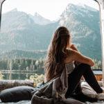 Frau in Baumwollschlafsack eingewickelt sitzt im Camper