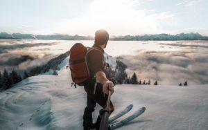 Mann mit Skirucksack im Schnee in den Bergen auf Skiern
