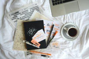 Handlettering Buch & Stifte auf Bettdecke mit Kaffe und Laptop