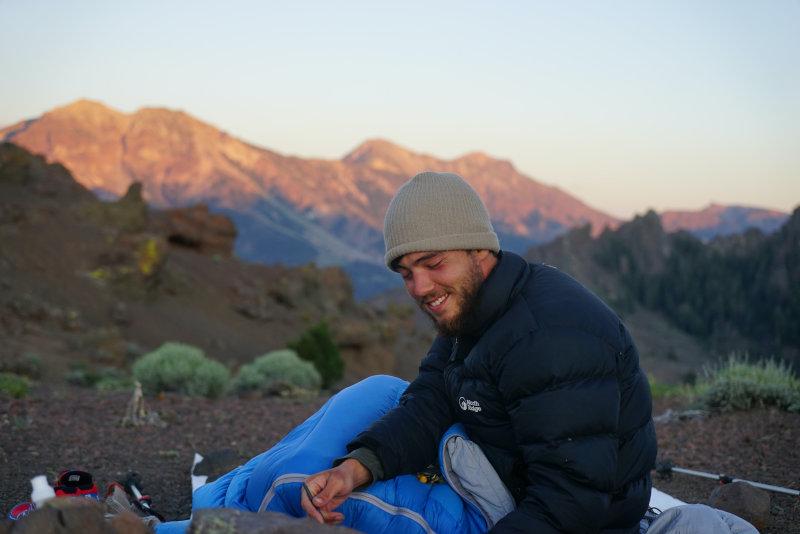 Mann sitzt in einem Schlafsack im Gebirge