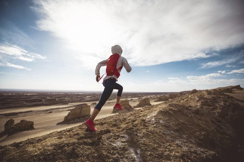 Trailrunner mit Rucksack läuft in Wüste