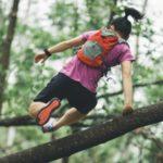 Trailrunner mit Rucksack springt über Baumstamm