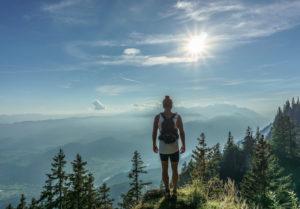 Wanderer mit Trinkrucksack auf einem Berg mit Landschaft im Hintergrund