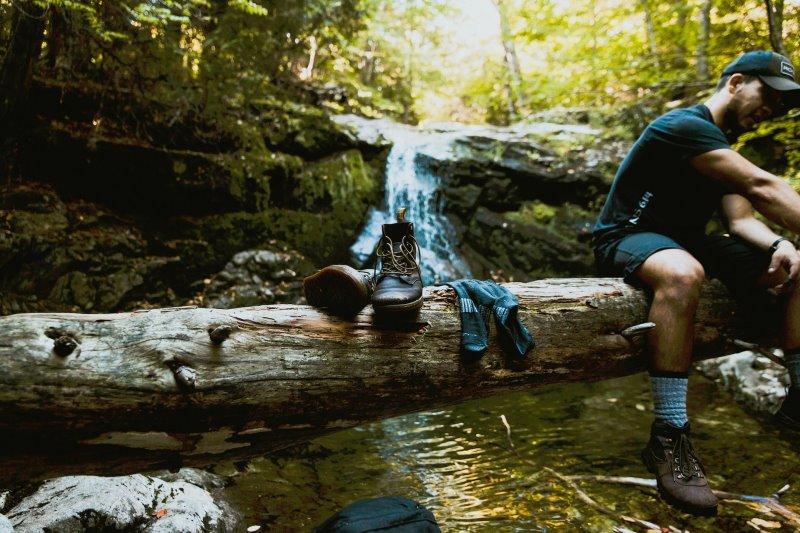 Mann sitzt auf Baumstamm neben ihm liegen Socken und Schuhe