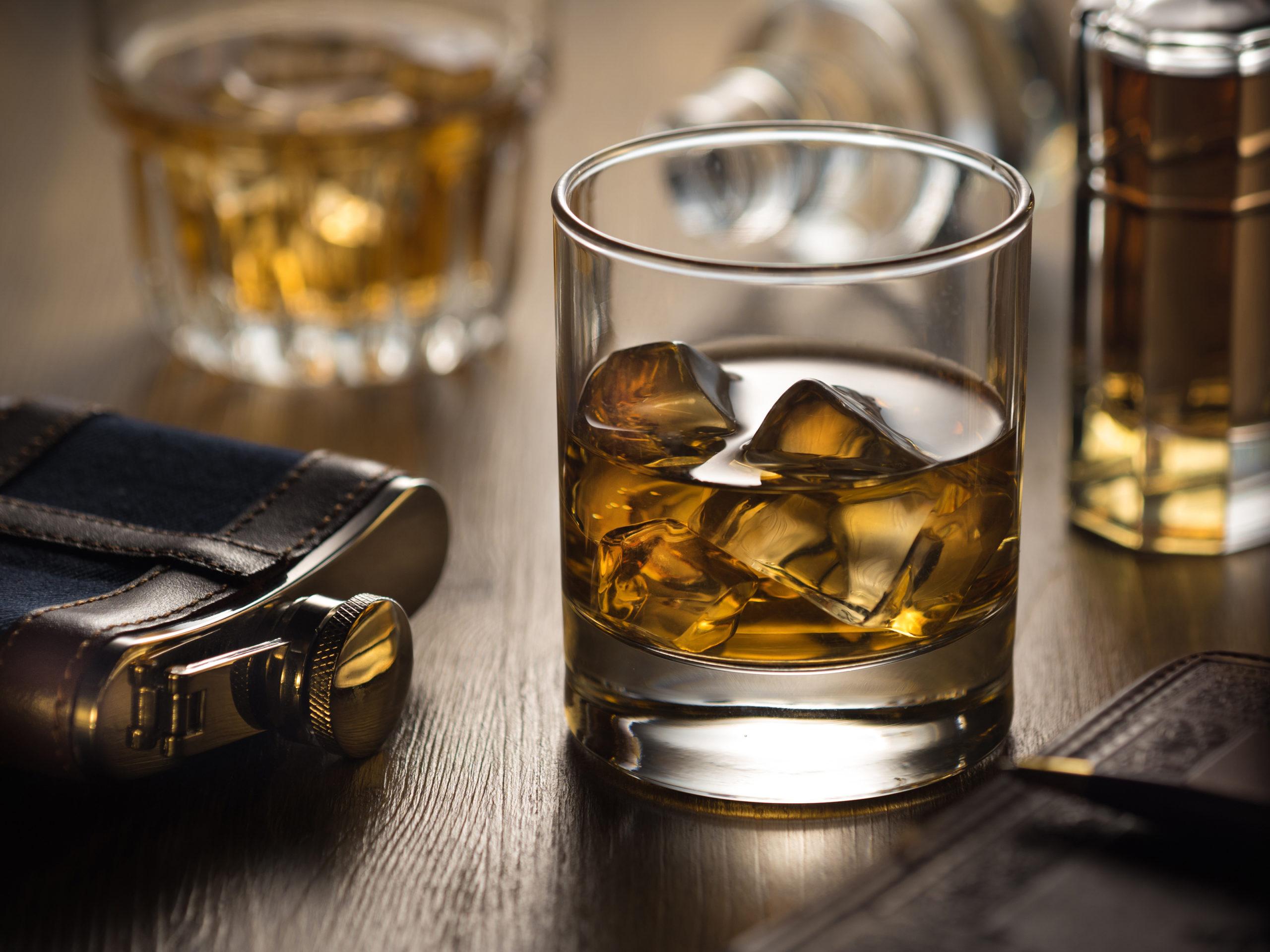 Whiskey im Glas neben einen Flachmann