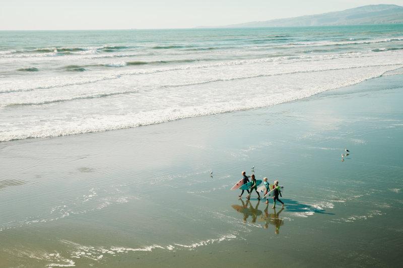 Kinder laufen am Strand mit Surfbrett im Neoprenanzug