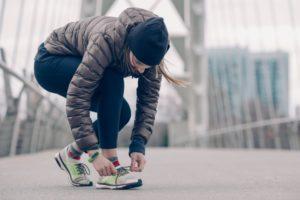 Frau bindet sich nach dem Laufen gehen die Schuhe im Winter.