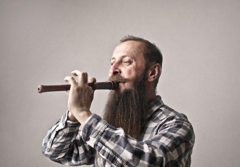 Mann spielt Blockflöte