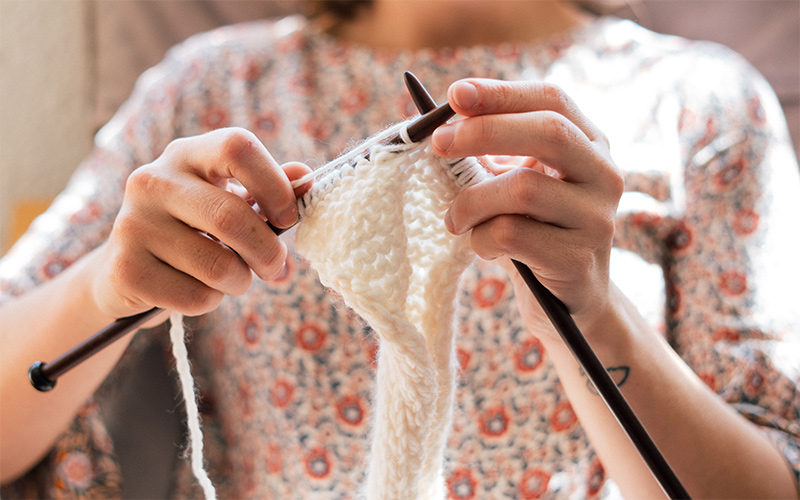 Eine Frau, die mit Stricknadeln strickt