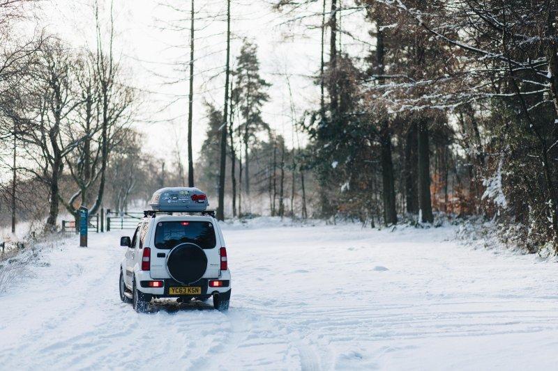 Auto mit Skibox im Schnee