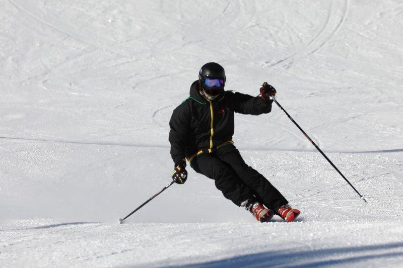 Der Skifahrer fährt mit einer Carving-Skibindung, um optimal zu carven.