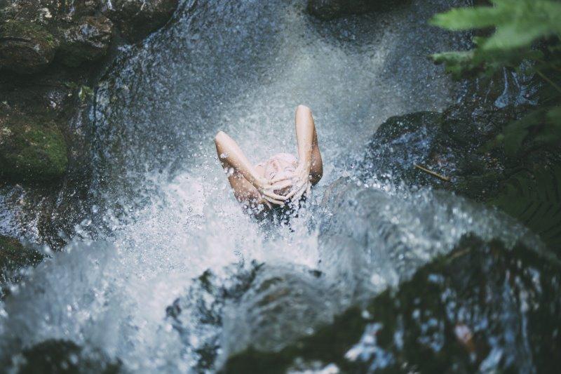 Eine Frau duscht in einem Wasserfall