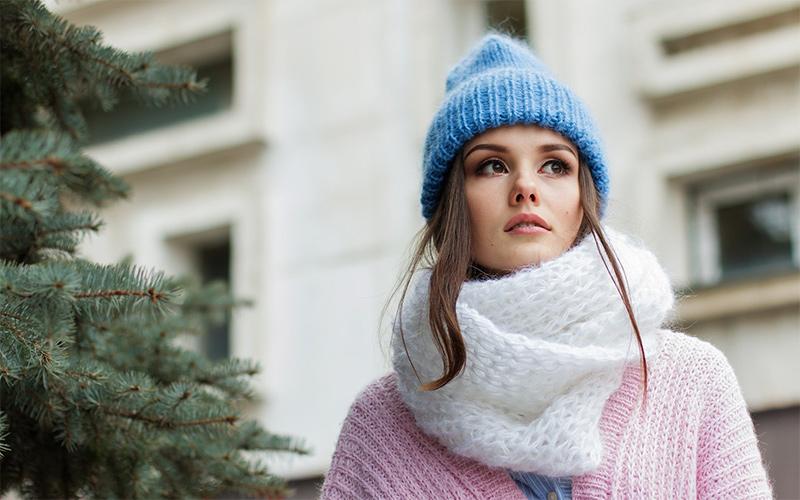 Eine Frau, die einen Loop Schal aus Wolle trägt