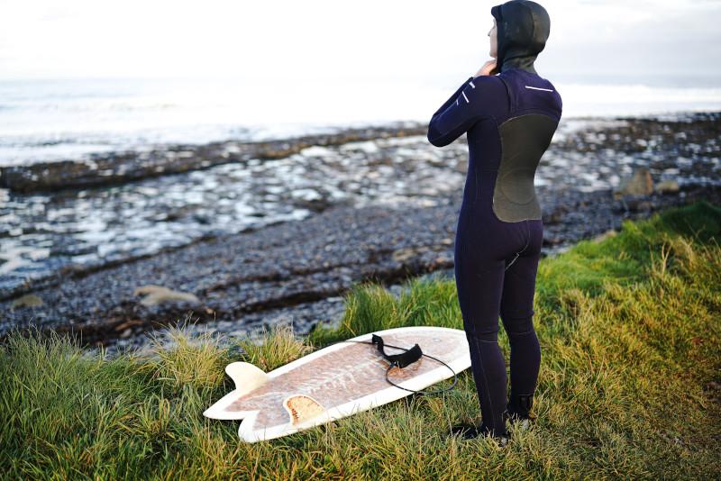 Frau im Winterneoprenanzug und Surfing Zubehör