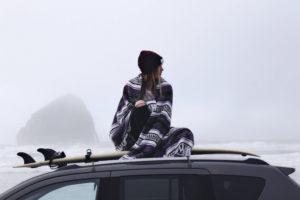 Frau mit Surfboard und wärmenden Poncho um die Schultern