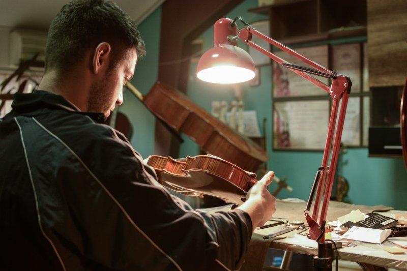 Geigenbauer begutachtet das Aussehen einer Geige