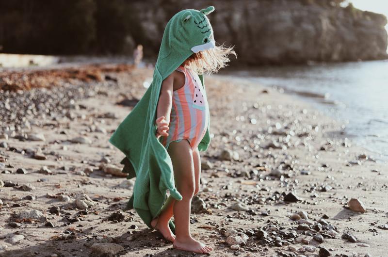 Kleines Kind mit Kapuzenponcho als Windschutz