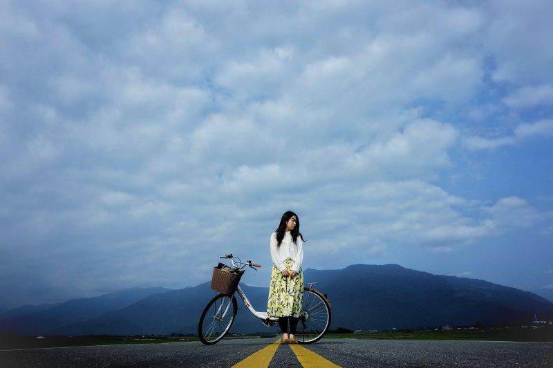 Ein Mädchen und ihr Tourenrad stehen auf einer befestigten Straße