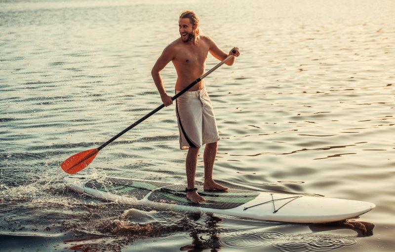 Mann steht auf einem aufblasbaren SUP Board