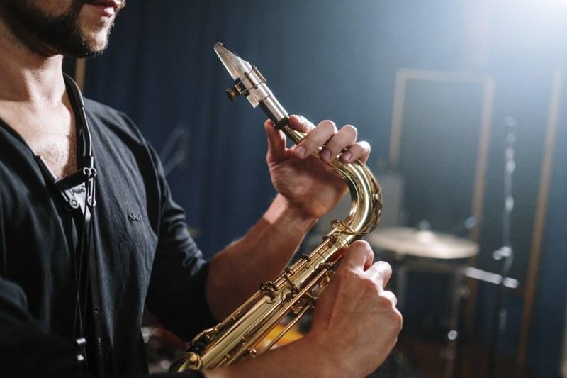 Mann hält den S-Bogen seines Saxophons fest