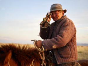 Mann auf einem Pferd mit einem Monokular